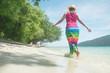 a beautiful carefree Woman relaxing at the beach enjoying her sun dress freedom wear.