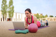 fit woman watching online fitness program and doing workout infront of a laptop on a mat