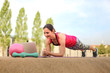 sporty and strong woman making planks infront of a laptop while watching online Fitness program on a mat in the park