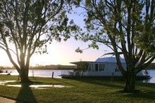 Evening At The Murray River In Australia With Houseboat Anchored To The Shore