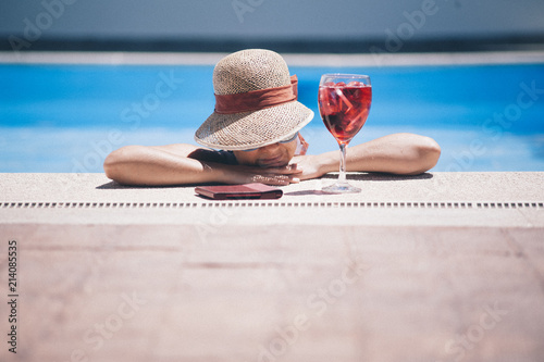 attractive girl with hat in the pool and glass of red soda