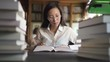 Female asian student in white shirt and stylish round glasses reading books in the library. Indoors. Portrait.