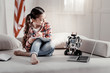 Robot as a model. Talented beautiful little girl picturing her toy watching cartoon while spending her leisure