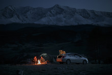 Couple In Camping With Campfire At Night On Mountain Background
