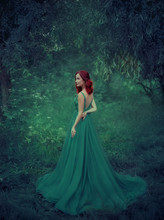 Red-haired Girl In A Green, Emerald, Luxurious Dress In The Floor, With An Open Back And A Long Train. The Princess Walks In A Fairy Forest. Photo From The Back. Artistic Retouching