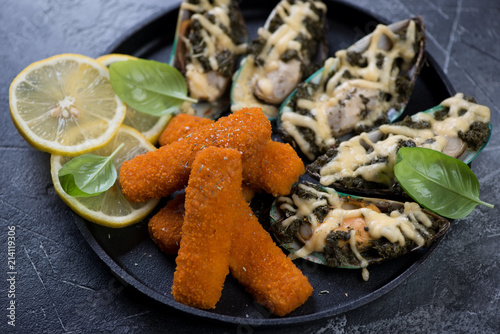 In de dag Assortiment Metal tray with roasted fish fingers and baked mussels with spinach and cheese, selective focus