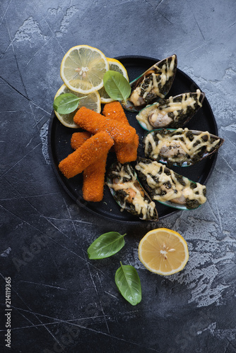 In de dag Assortiment Seafood snacks including baked mussels and fried fish sticks or breaded fish fillet with lemon, above view on a dark grey concrete background