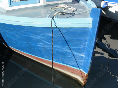 Foto  Prow of a blue wooden fishing boat moored in the harbor