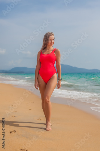 Fotobehang womenART Sexy woman in red swimsuit staying on the beach near ocean, Phuket