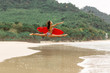 Outdoor photo of gorgeous young woman in fashion bikini doing jump split leap with red surfboard. Summer sunny day sport surfing concept, seascape with girl, beach, beautiful waves, blue water.