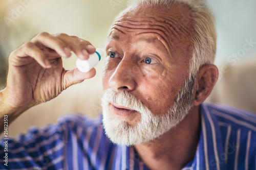 Fotomural  Elderly Person Using Eye Drops