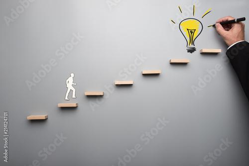 Foto op Canvas Licht, schaduw Paper cutout shape of a man climbing steps towards light bulb