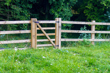 A Simple And Plain New Wooden Fence Stretching Along A Meadow Before A Wood In The English Countryside