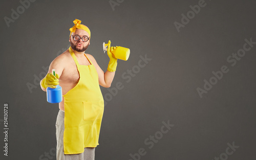 Cuadros en Lienzo Funny fat cleaning man in an apron on cleaning on a background for text