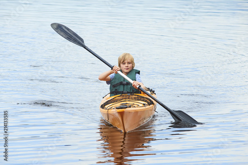 Active happy child. Teenage school boy having fun enjoying adventurous experience kayaking on the lake on a sunny day during summer vacation