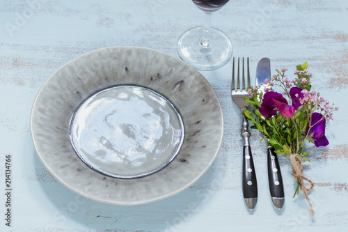 Papiers peints Con. ancienne Rustic table setting with purple flowers and glass of red wine on light wooden table.