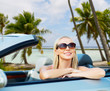 travel, road trip and summer holidays concept - happy young woman in convertible car over exotic beach with palm trees in french polynesia background