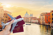 Plane Travel Concept, Hand Holding Passports With Plane Against Venice Cityscape