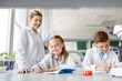 education, science and children concept - teacher and students studying chemistry at school laboratory and writing to workbooks