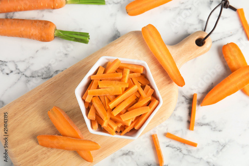 Bowl with cut ripe carrot on wooden board, top view