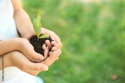 Foto op Canvas Planten Woman and her child holding soil with green plant in hands on blurred background. Family concept