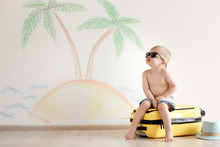 Adorable Little Child Playing Traveler With Suitcase Indoors