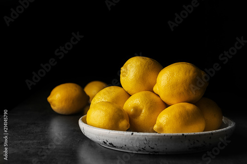Plate with whole lemons on table against dark background