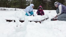 Grandmother With Adult Daughter And Young Granddaughter Making Snowman At Winter