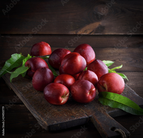 red ripe peaches nectarine on a brown wooden board