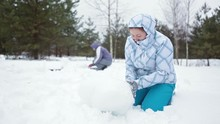 Two Caucasian Women Making Sculptures From Snow At Winter Field