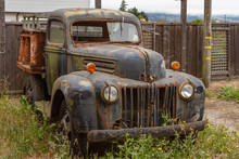 Ancient Rusting Old Pickup Truck In Front Of A Wooden Fence