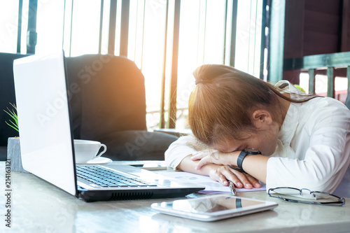 Fotografía  Freelancer asian businesswoman tired after working at workplace her sleeping on workplace table near windows at evening with digital laptop computer
