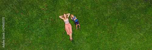 Foto  Mom and son are lying on the grass in the park, photos from the drone, quadracop