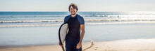 Handsome Sporty Young Surfer Posing With His Surfboard Under His Arm In His Wetsuit On A Sandy Tropical Beach BANNER Long Format