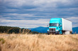 canvas print picture - Blue modern big rig semi truck transport semi trailer on scenic road with grass forest mountain and cloudy sky