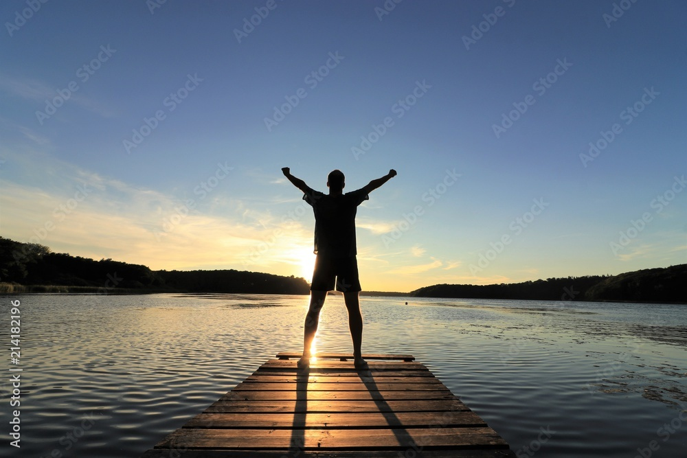 Fototapeta Man standing at a landing stage in nature raising his arms to the sky
