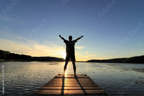 Slika na platnu Man standing at a landing stage in nature raising his arms to the sky
