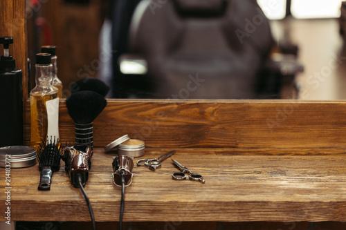 Fotografia  barber tools on wooden shelf and mirror in barbershop