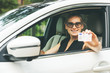 happy young woman showing her driver license through the car window