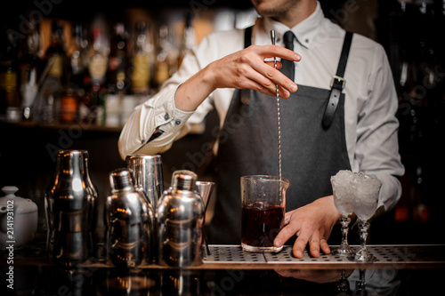 Photo Bartender stirring fresh summer alcoholic cocktail in glass