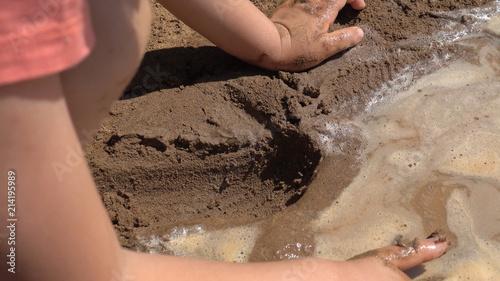 Child kneads mud in the sandbox. Canvas Print