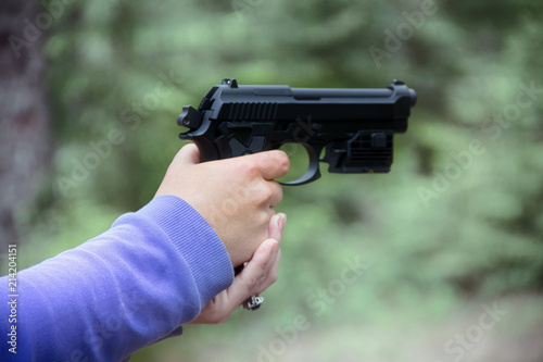 Fotografie, Obraz  Woman shoots from air gun in forest
