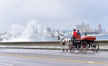 Tourists In A Horse And Carriage Ride Along El Malecon, Havana, Cuba