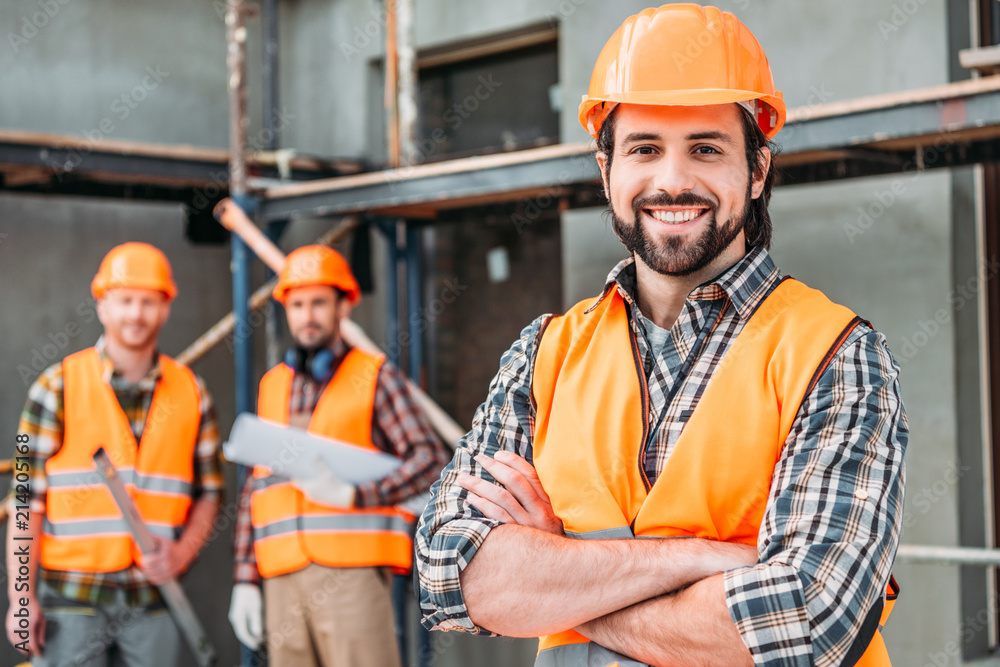 Fototapeta handsome smiling builder standing at construction site with crossed arms while his colleagues standing blurred on background