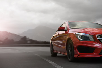 red business car speeding on a mountain highway with motion blur