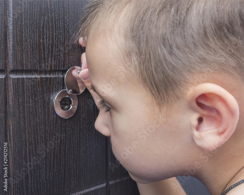 Fotografie, Obraz A 5 year old boy is looking at the peephole, child alone at home.