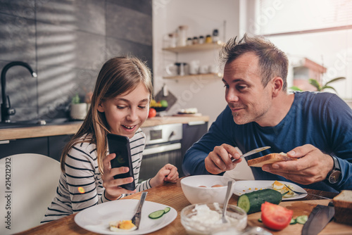 Daughter showing text message on smart phone to a father