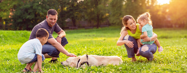 happy family is having fun with golden retriever - family playing with dog in park.
