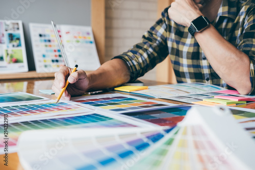 Fotografie, Obraz Young creative Graphic designer using graphics tablet to choosing Color swatch s