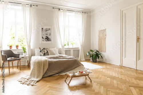 Obraz Grey armchair next to bed with blanket in bright bedroom interior with poster and windows. Real photo - fototapety do salonu